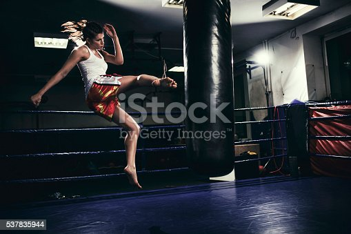 istock Female muay thai fighter training with a punching bag 537835944