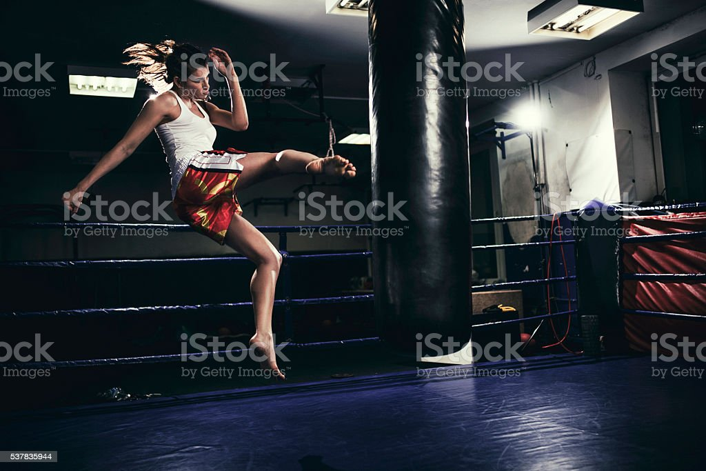 Female muay thai fighter training with a punching bag stock photo