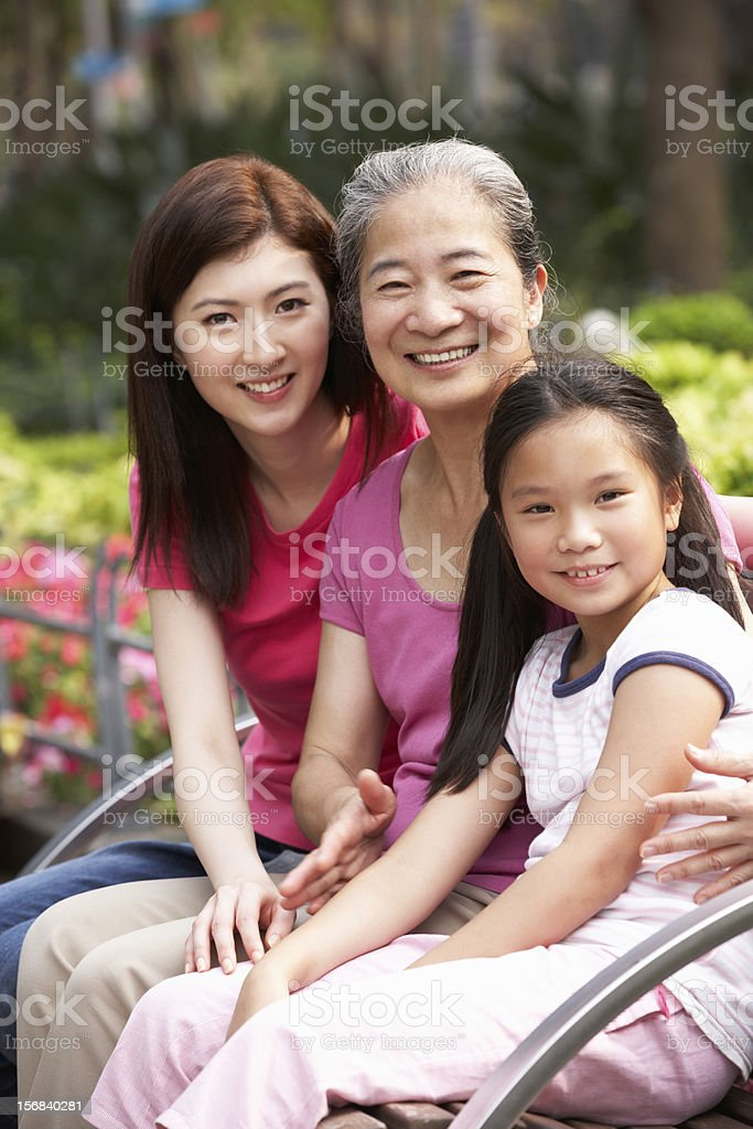 Female Multi Generation Chinese Family Group Sitting In Park stock photo