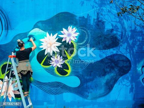 istock Female mural artist at work 1273321821