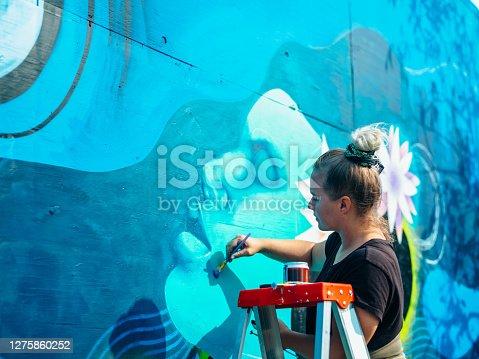istock Female mural artist at work 1275860252