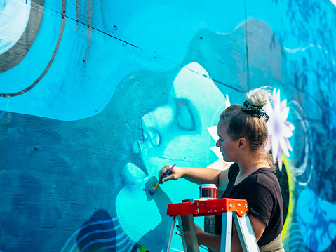 Female mural artist creating art on the wall exterior in public park in the city.