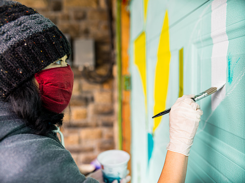 Female mural artist creating art on the garage door of the private home in the city.