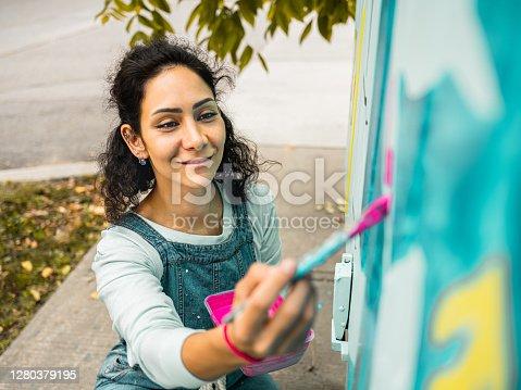 istock Female mural artist at work 1280379195