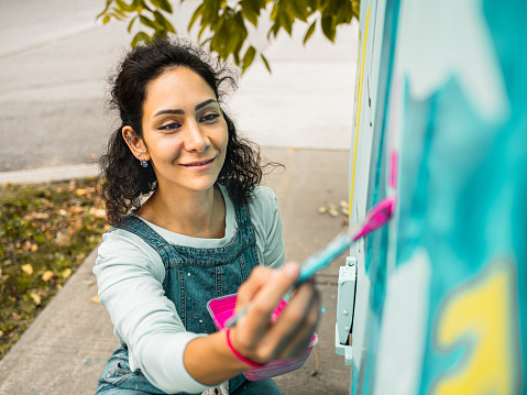 Female mural artist creating art on the public utility box on the street corner in the city.