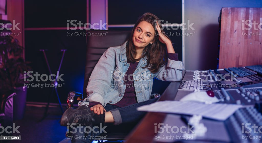 Female music composer sitting by sound mixing console stock photo