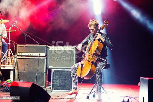 Young female musician playing cello on stage as a member of rock and roll band in concert.