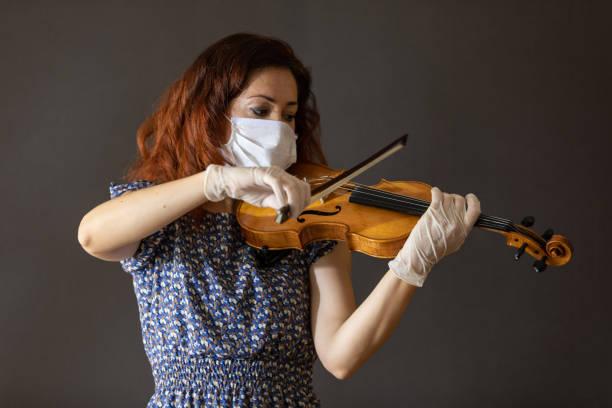 Female musician who plays violin in covid19 outbreak quarantine days. stock photo