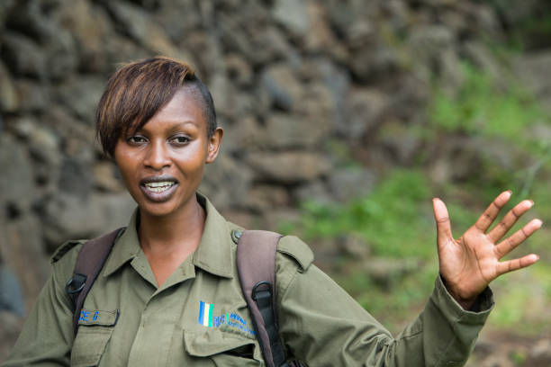 Female national park ranger at a Gorilla Trekking in Rwanda Kinigi, Rwanda - January 8, 2016: A female ranger of the Parc National des Volcans in Rwanda during her explanations to tourists before they are starting their safari walk to the Mountain Gorillas. park ranger stock pictures, royalty-free photos & images