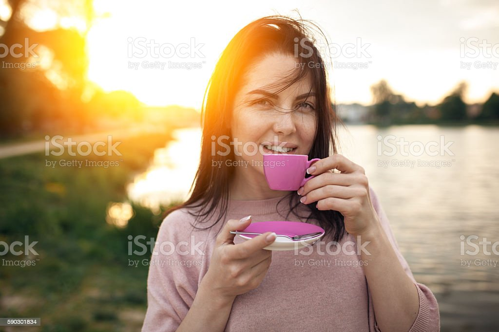 female near lake or river and keeps cup of coffee; royaltyfri bildbanksbilder