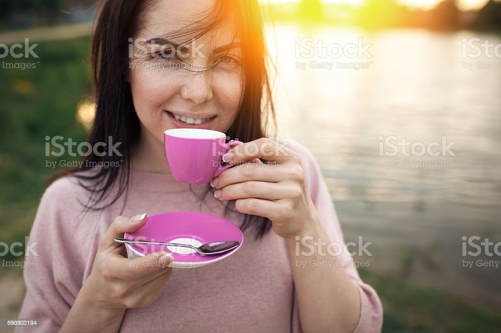 female near lake or river and keeps cup of coffee; Стоковые фото Стоковая фотография
