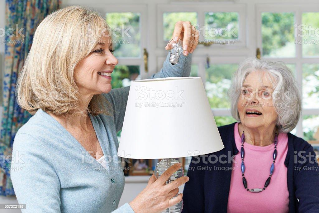 Female Neighbor Helping Senior Woman Change Lightbulb In Lamp stock photo