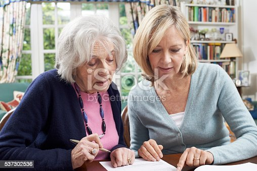 istock Female Neighbor Helping Senior Woman To Complete Form 537302536