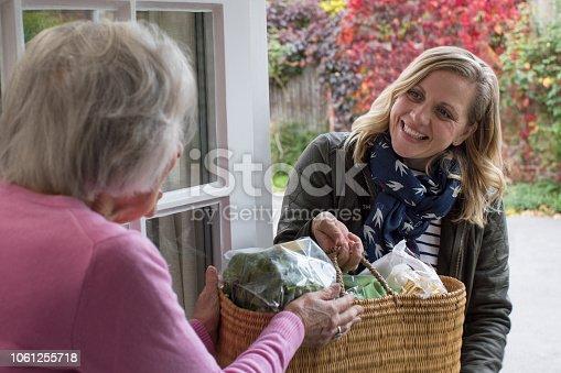 istock Female Neighbor Helping Senior Woman With Shopping 1061255718