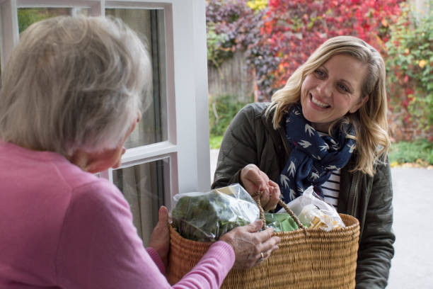 female neighbor helping senior woman with shopping - a helping hand stock pictures, royalty-free photos & images