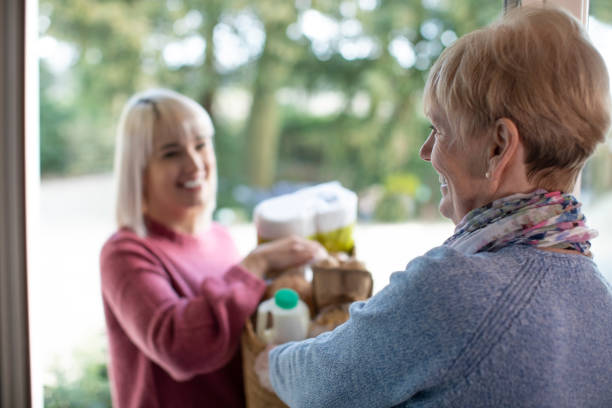 female neighbor helping senior woman with shopping - grocery home foto e immagini stock