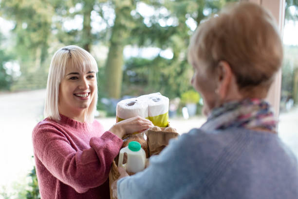 Female Neighbor Helping Senior Woman With Shopping Female Neighbor Helping Senior Woman With Shopping a helping hand stock pictures, royalty-free photos & images