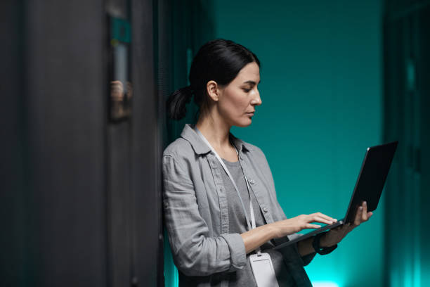 Female Network Engineer using Laptop Side View stock photo