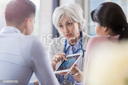 While holding a digital tablet with a brain scan on the screen, a female neurologist with gray hair makes eye contact with her female patient's husband and gestures toward the scan. She is explaining her patient's diagnosis.