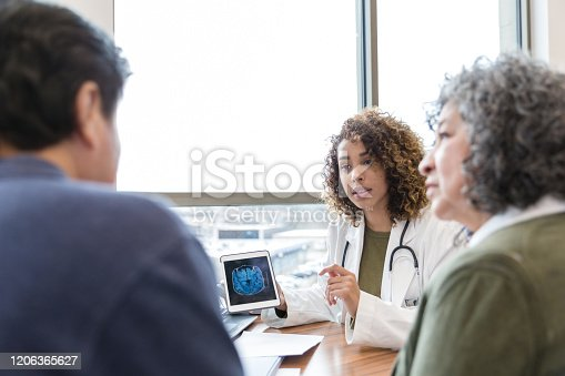 Serious female neurologist shows a senior male patient an MRI image of his brain. The doctor discusses a serious diagnosis with the patient and the patient's wife.