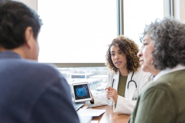 Female neurologist discusses brain scan with patient Serious female neurologist shows a senior male patient an MRI image of his brain. The doctor discusses a serious diagnosis with the patient and the patient's wife. neurodegenerative disease stock pictures, royalty-free photos & images