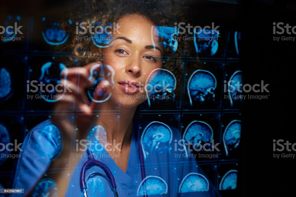 female neurosurgeon a female doctor or surgeon is analysing the digitally generated scans of a human brain 30-39 Years Stock Photo