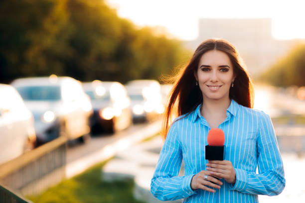 Female News Reporter on Field in Traffic stock photo