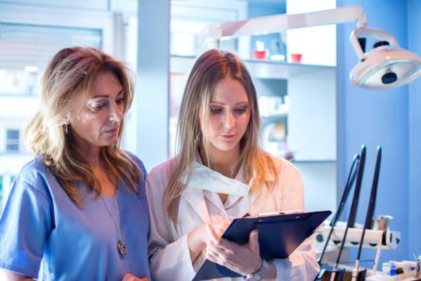 kvinnlig sjuksköterska och tandläkare läsa patientens tandläkare resultat från urklipp i tandläkare kontor. - two dentists talking bildbanksfoton och bilder