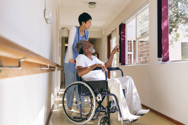 Female nurse and senior male patient interacting stock photo