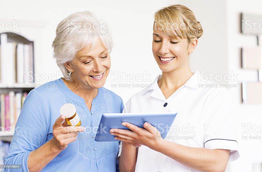 Female Nurse And Senior Woman Using Digital Tablet. royalty-free stock photo