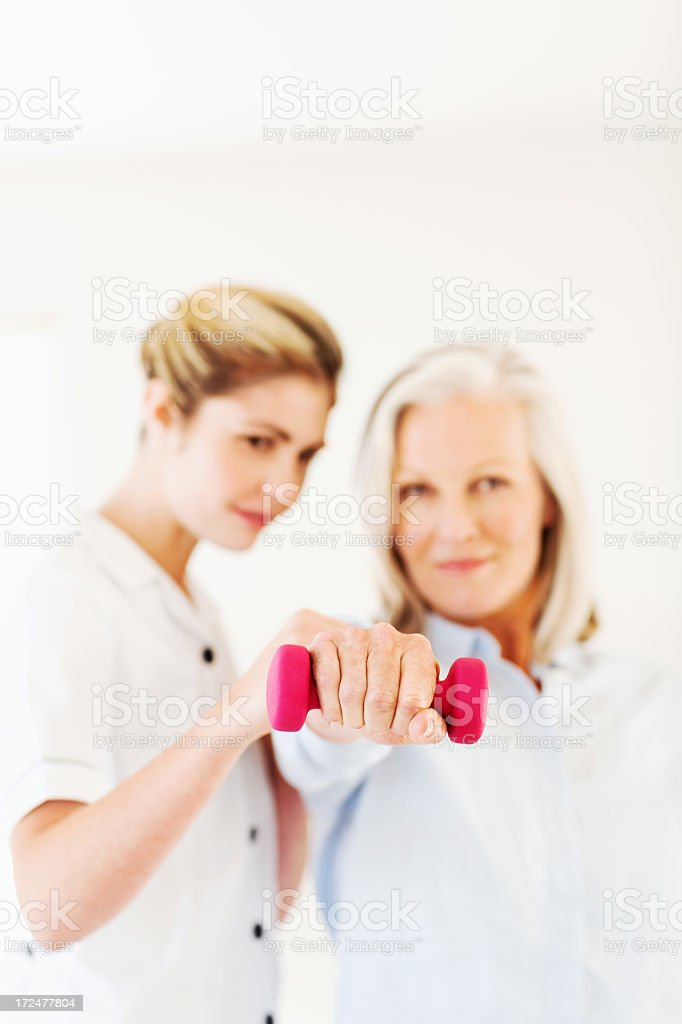 Female Nurse Assisting Woman In Lifting Dumbbell stock photo