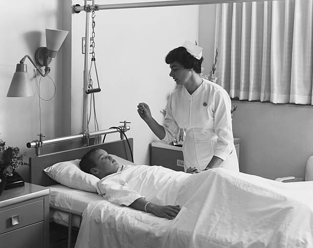 Female nurse checking boy's temperature  20th century stock pictures, royalty-free photos & images