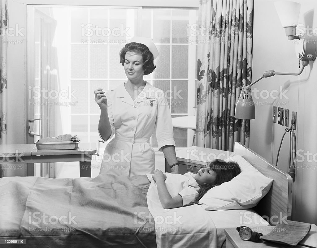 Female nurse checking girl's temperature stock photo