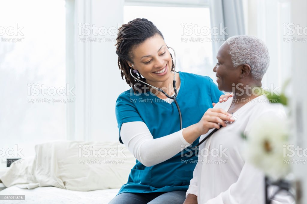 Female nurse checks patient's vital signs stock photo
