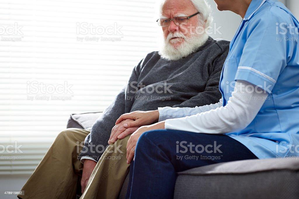 Female nurse consoling elderly patient stock photo