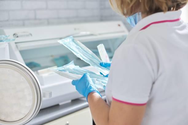 Enfermera femenina haciendo esterilización de instrumentos médicos dentales en autoclave - foto de stock