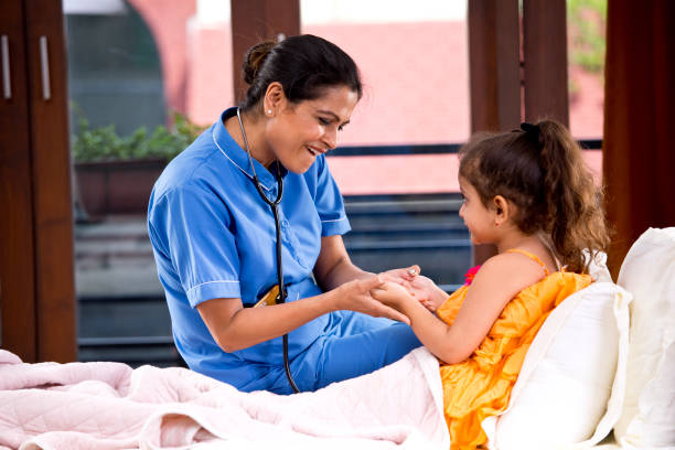 Female nurse having fun with girl lying on bed during medical house call stock photo