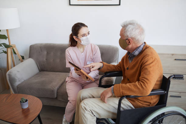 Female Nurse Helping Disabled Senior Man with Technology stock photo