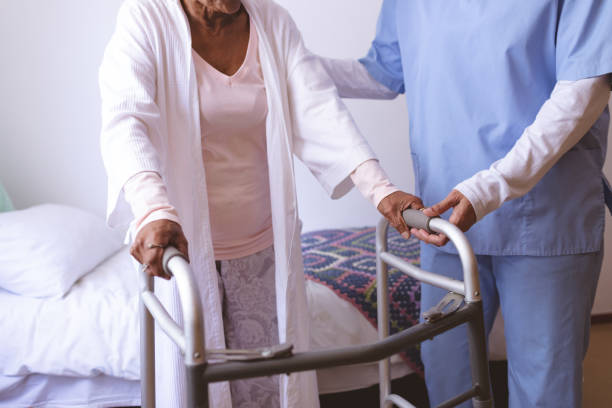 Female nurse helping senior female patient to stand with walker stock photo