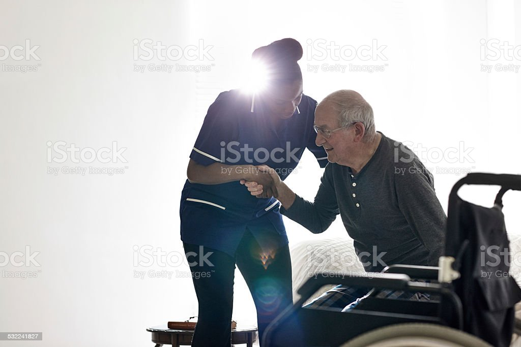 Female nurse helping senior man get up from bed stock photo