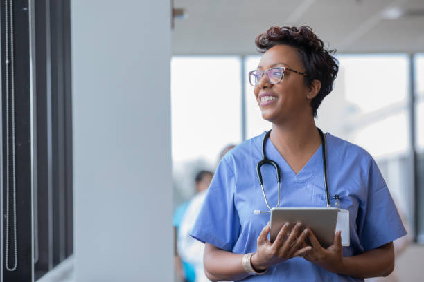 Female nurse holding digital tablet smiles while looking out window stock photo