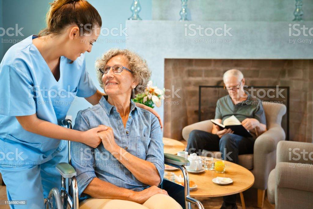 Smiling female nurse holding hands of disabled elderly woman. Retired...