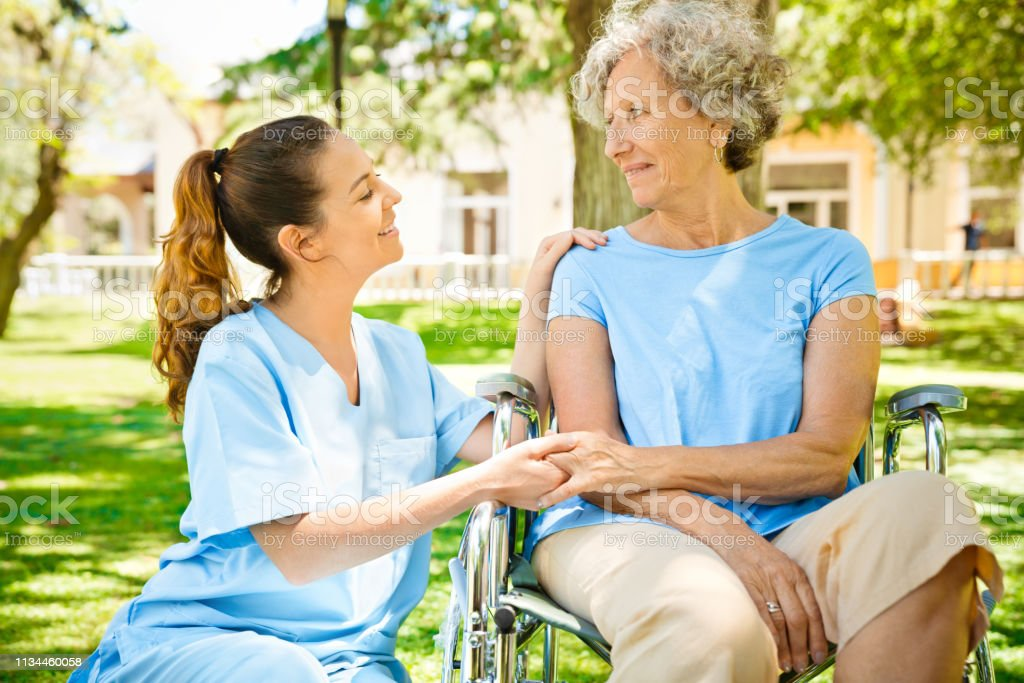 Healthcare worker holding hands of retired female sitting on...
