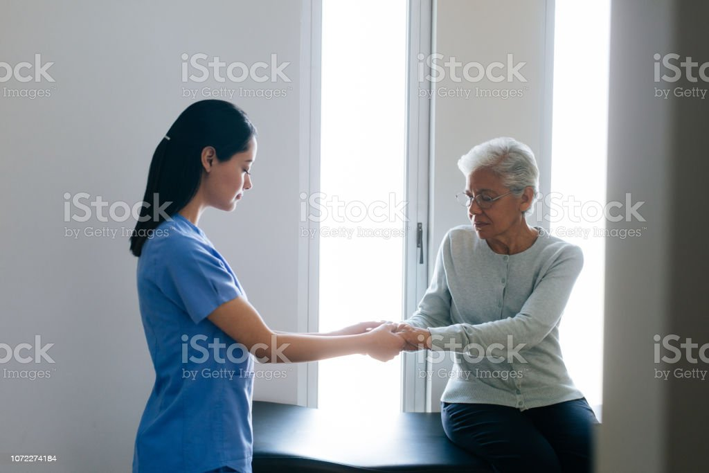 A latin female nurse holding the hands of a senior female patient.