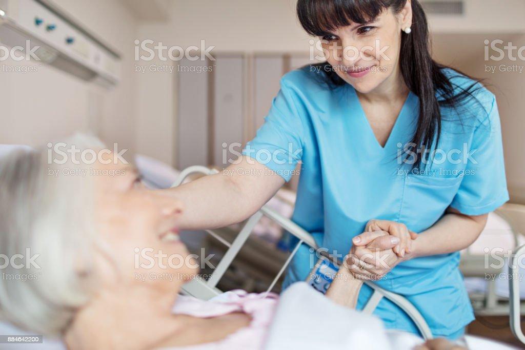 Female nurse holding senior woman's hand stock photo