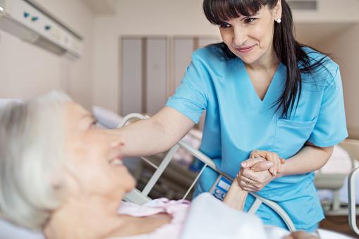 Female Nurse Holding Senior Womans Hand Stock Photo - Download Image Now
