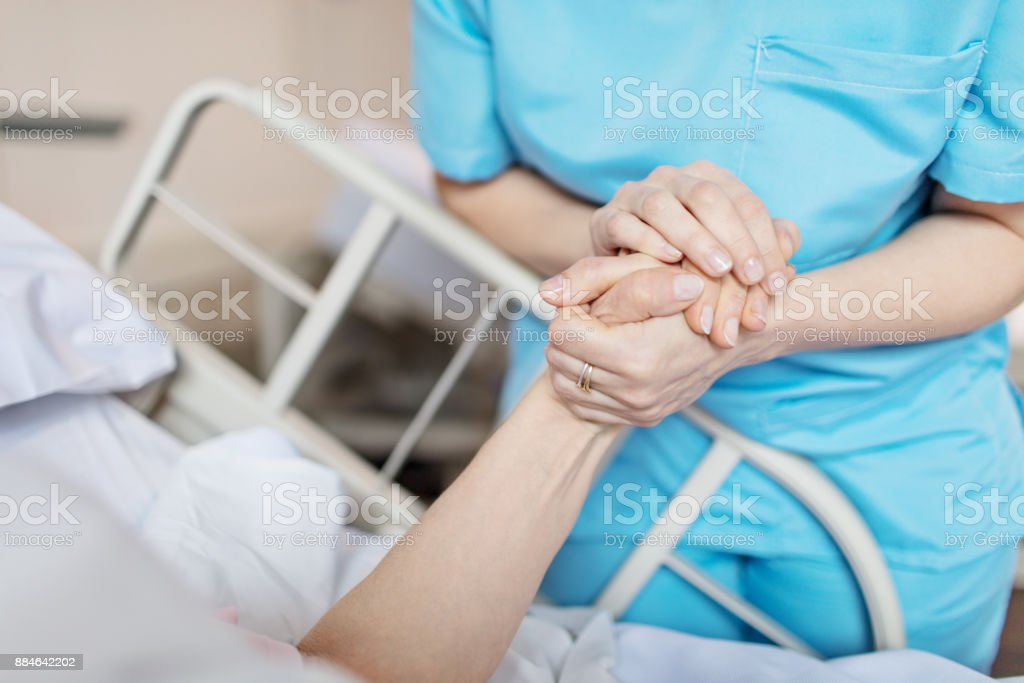 Female nurse holding senior woman's hand royalty-free stock photo