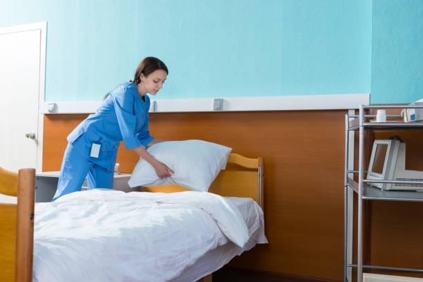 krankenschwester hält eine weiße kissen über das krankenbett in der spitalabteilung - verwandlungskissen stock-fotos und bilder