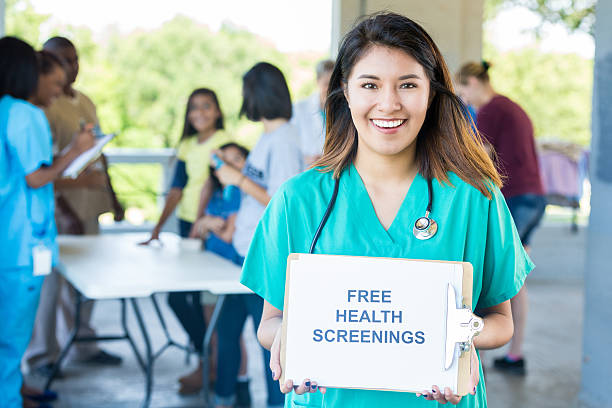 Female nurse holds 'Free Health Screenings' sign at health fair stock photo