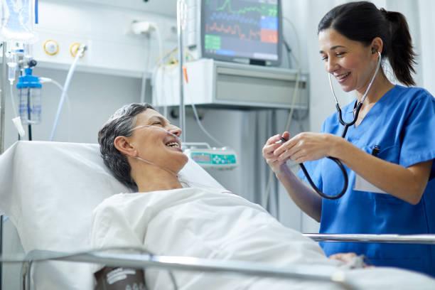 Eine Krankenschwester hört mit einem Stethoskop das Herz eines Patienten. – Foto
